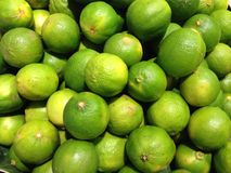 Gröna citroner i fruktmarknaden Arkivbild