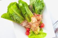 Gröna cos som slås in i bacon på den vita maträtten Arkivbilder