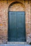 Gröna dörrar i tegelstenvalvgång Arkivbild