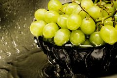 Gröna druvor i en svart platta under rinnande vatten arkivbild
