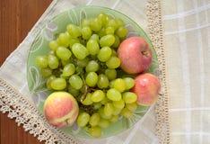 Gröna druvor och röda äpplen på en platta Royaltyfria Bilder