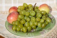 Gröna druvor och röda äpplen på en platta Royaltyfri Fotografi