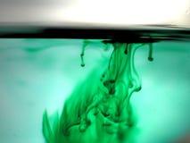 Gröna färgpulverpigmentdroppar i vatten Smokey Droplet Texture royaltyfri fotografi