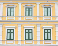 Gröna fönster på den orange väggen Arkivfoton