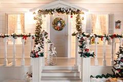 Gröna girlander av gran eller sörjer filialer med den röda och guld- julleksakdörren på verandan Arkivbilder