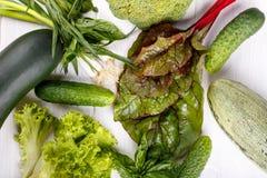 Gröna grönsaker på vit träbakgrund royaltyfri foto