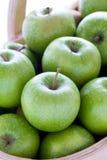 Gröna grannysmedäpplen i en trätrug royaltyfri foto