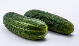 gröna gurkor på en vit bakgrund Arkivfoto