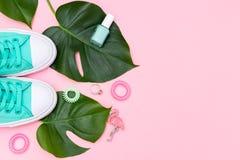 Gröna gymnastikskor och gröna tropiska sidor Moderiktig kvinnlig accessor Arkivbilder