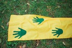 Gröna handprints på gult tyg royaltyfria foton
