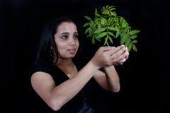 gröna holdingväxtkvinnor Arkivfoto