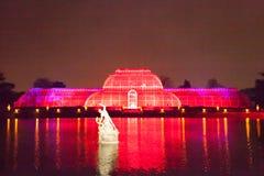 Gröna hus på Kew trädgårdar tänder upp rött royaltyfri foto