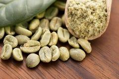 Gröna kaffebönor med bladet Arkivbilder