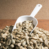Gröna kaffebönor och skopa Arkivfoto