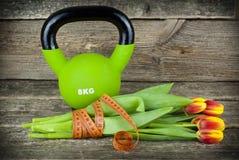Gröna kettlebells och bundet med en mäta bandbukett av tulpan blommar på en träbakgrund arkivfoton