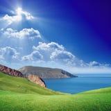 Gröna kullar, blått hav och himmel Fotografering för Bildbyråer