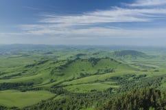 Gröna kullar i bergdalen och molnig himmel Arkivbilder