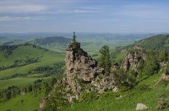 Gröna kullar i bergdalen och molnig himmel Arkivbild