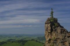 Gröna kullar i bergdalen och molnig himmel Arkivfoton
