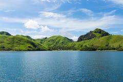 Gröna kullar i havet Arkivbild
