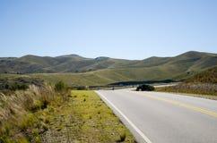 Gröna kullar och väg Arkivfoton