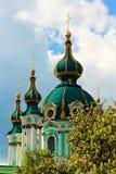 Gröna kyrkliga kupoler och ett kastanjebrunt träd Royaltyfri Bild