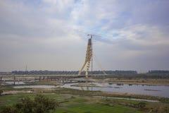 Gröna lantgårdfält nära enbliven bro under konstruktion och en tornkran över den Yamuna floden mot en blå himmel royaltyfria bilder