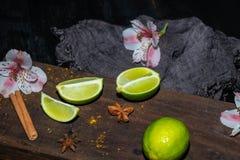Gröna limefruktskivor på ett brunt bräde, bredvid lösa orkidéblommor och mörkt tyg mot en svart bakgrund royaltyfria foton