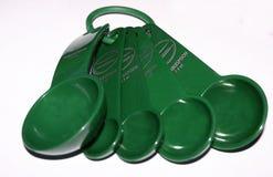 gröna mätande skedar Arkivfoton