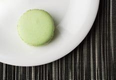 Gröna Macaron på den vita plattan Arkivfoton
