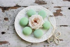 Gröna makron på en vit platta Royaltyfri Foto