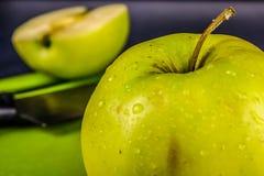 Gröna nya äpplen som huggas av upp på det gamla brädet På en trätabell arkivfoton