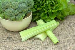 Gröna nya grönsaker hel broccoli i en bunke med grönsallat och selleri på bordduken Royaltyfri Foto