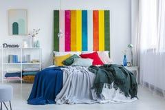Gröna och blåa filtar på en vit säng med regnbågebedhead i vitt, scandisovruminre Verkligt foto royaltyfria foton