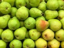 Gröna och gula päron i jordbruksprodukterfack Arkivbild