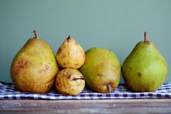 Gröna och gula päron på en kökshandduk Royaltyfri Fotografi