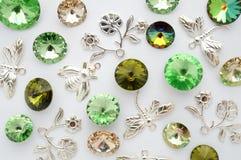 Gröna och guld- kristaller och metallbin och blommor och sländor på vit bakgrund Royaltyfri Foto