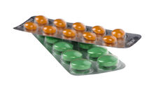 Gröna och orange preventivpillerar i blåsor som isoleras på vit Royaltyfri Bild