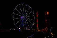 Gröna och purpurfärgade Juli 4th Ferris Wheel i karneval på natten Arkivfoton