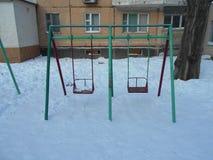 Gröna och röda barns gunga i snön parkerar område av ‹för †staden Arkivbild