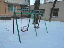 Gröna och röda barns gunga i snön parkerar område av ‹för †staden Royaltyfria Bilder