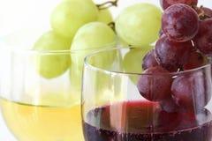 Gröna och röda druvor på vit- och rött vinexponeringsglasen Arkivfoton
