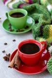 Gröna och röda koppar kaffe med kaffe Bence, anisstjärna Arkivbild