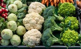 Gröna och vita broccoli, blomkålar, kål och rovor på försäljning Grönsakbakgrund och naturlig modell royaltyfria bilder