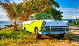 Gröna och vita Ford Fairlane som parkeras på stranden Arkivbild