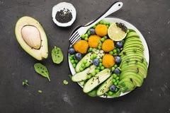 Gröna olika grönsaker, avokadon, gurkor, kiwin, blåbär, micro gör grön, ost klumpa ihop sig, falafelen, kikärtar överkant Royaltyfri Bild