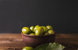 Gröna oliv i en keramisk bunke på en träbakgrund Arkivfoton