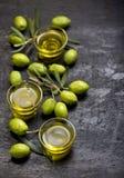 Gröna oliv, olivgrön filial och olivolja på ett mörkt träbräde royaltyfri bild