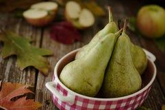 Gröna päron i rosa färgmaträtt med äpplen i lantlig inställning Arkivfoton