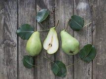 Gröna päron med blad på den gamla trätabellen Kicken metar beskådar Arkivbilder